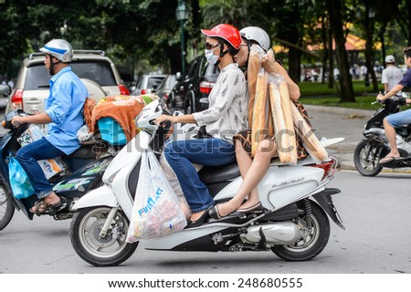HANOI, VIETNAM - SEP 23, 2014: Unidentified Vietnamese woman on a motorbike with bread baggets. 92% of Vietnamese people belong to the Viet ethnic group - stock photo