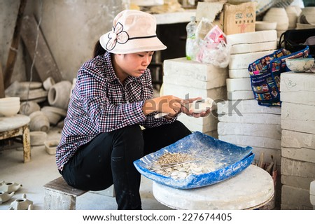 HANOI, VIETNAM - SEP 24, 2014: Unidentified Vietnamese woman works at the ceramic workshop. Ceramic art is very popular in Asian culture - stock photo