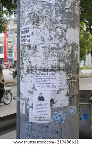 Hanoi, Vietnam - Sept 21, 2014: Advertising papers on electricity pole on Thanh Xuan st, Hanoi, Vietnam