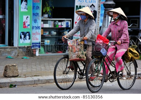 HANOI, VIETNAM - SEPTEMBER 17: Unidentified womans rides bicycle along Ma May street in Hanoi, Vietnam on September 17, 2010. Transportation Police Bureau estimated some 20 million bicycles in Vietnam
