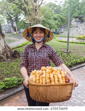 HANOI, VIETNAM,  19TH MARCH 2017: A local lady in Hanoi selling sweet treats. The lady is wearing a traditional cone hat common on Vietnam