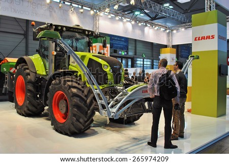 HANOVER, GERMANY, 20 MARCH 2015 - Cebit visitors looking at a Claas tractor with digital technology at Cebit, the biggest IT trade fair in the world. - stock photo