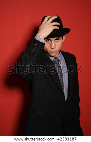 Hansome Young man in suit over red wall