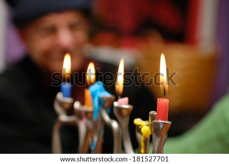 Hanukkah, a Jewish celebration. Candles burning in the menorah, the old man in the background. - stock photo