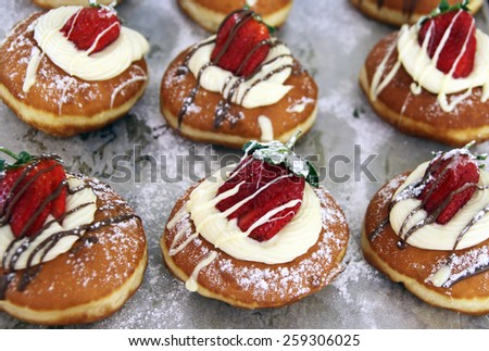 Hanukkah donuts decorated with fresh strawberries and cream - stock photo