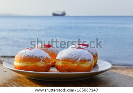 Hanukkah donuts with jam on background of the Red Sea, Israel  - stock photo