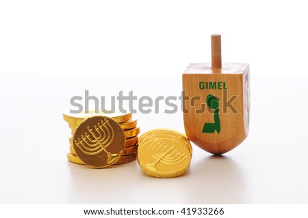 Hanukkah dreidel and gelt set against  white background.
