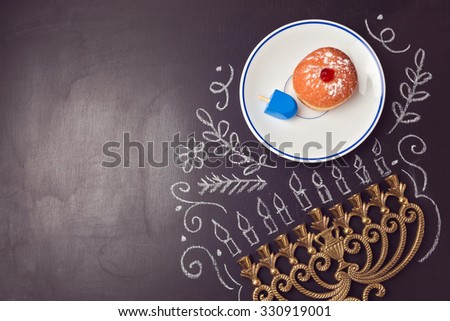 Hanukkah holiday background with menorah and sufganiyot over chalkboard. View from above - stock photo