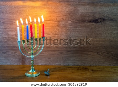 Hanukkah menorah and silver dreidel  on wooden table. - stock photo