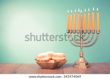 Hanukkah menorah with burning candles and donuts. Retro old style filtered photo - stock photo
