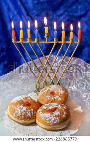 Hanukkah menorah with burning candles and traditional doughnuts - stock photo