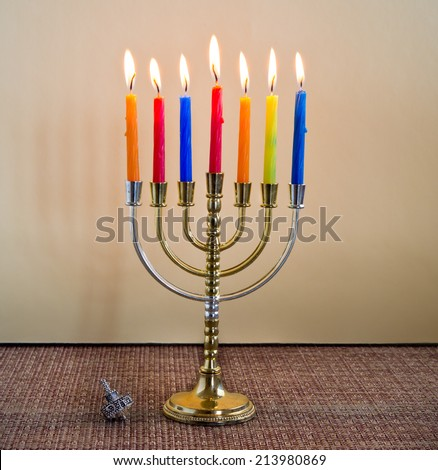 Hanukkah menorah with candles and silver dreidel. - stock photo