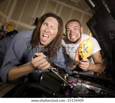 Hapless mechanics working on car engine getting in each others way - stock photo