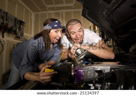 Hapless mechanics working on car engine with grinder - stock photo