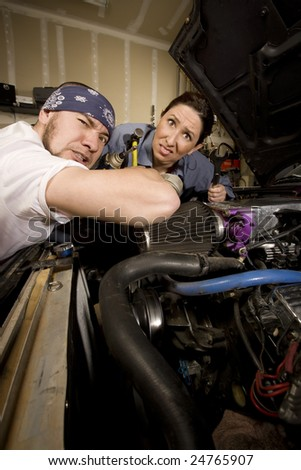 Hapless mechanics working on car with all the wrong tools - stock photo