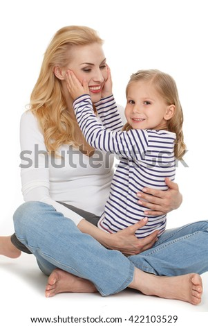 Happiest person in the world. Portrait of a little girl sitting on her cheerful mothers lap looking to the camera smiling at the studio isolated on white. - stock photo