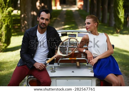 Happily married couple enjoying a beautiful day outdoors while leaning on their convertible antique car, handsome wealthy man and his gorgeous female posing outdoors, people spending time together  - stock photo