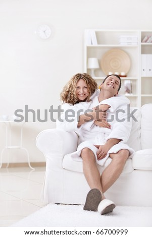Happily married couple in dressing gowns at home - stock photo