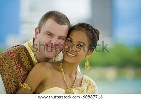 happily married couple in traditional thai wedding clothes posing in a park - stock photo