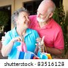 Happily married senior couple on a shopping strip together. - stock photo