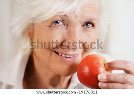 Happily senior woman holding red apple - stock photo
