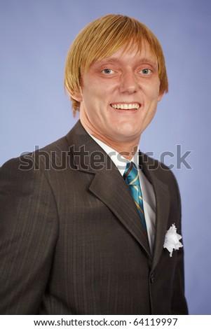Happily smiling groom on purple background - stock photo