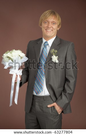Happily smiling groom with bunch - stock photo