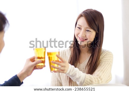 Happily smiling woman proposes a toast to her male friend, both raising glasses towards each other. Their glasses are filled with finest Japanese beer. - stock photo