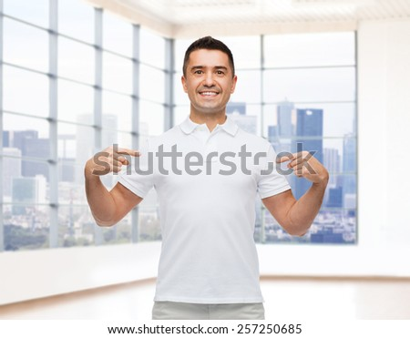 happiness, advertisement, fashion, gesture and people concept - smiling man in t-shirt pointing fingers on himself over empty apartment or office room with big window and city view background - stock photo