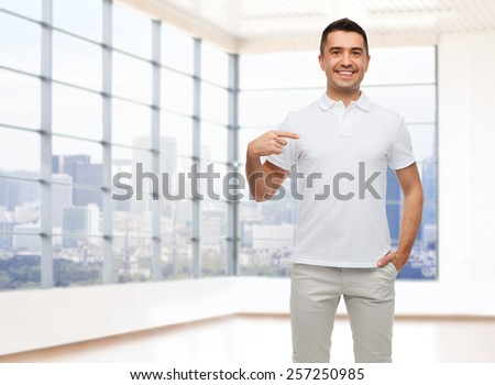 happiness, advertisement, fashion, gesture and people concept - smiling man in t-shirt pointing finger on himself over empty apartment or office room with big window and city view background - stock photo