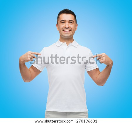 happiness, advertisement, fashion, gesture and people concept - smiling man in t-shirt pointing fingers on himself over blue background