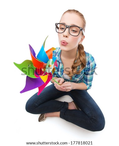 happiness and ecology concept - smiling woman in eyeglasses sitting on floor with windmill - stock photo