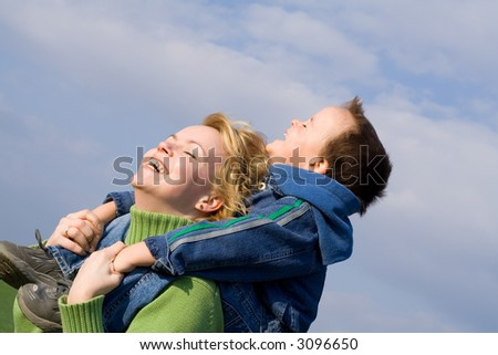 Happiness and fun - mother and son playing outdoors in spring - stock photo