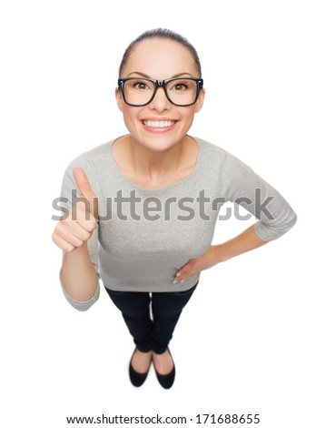 happiness and gesture concept - smiling asian woman in eyeglasses showing thumbs up - stock photo