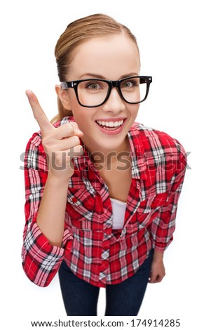 happiness and gesture concept - smiling teenager in eyeglasses with finger up - stock photo