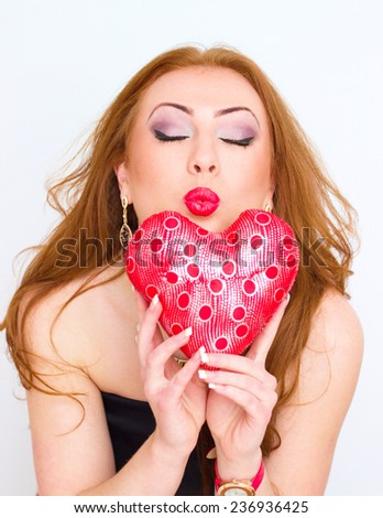 Happiness and love concept. Happy redhair girl young woman holding valentine red heart blowing kiss. Valentines day