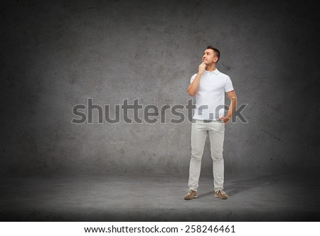 happiness and people concept - smiling man with hands in pockets looking up and thinking over concrete background - stock photo