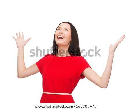 happiness and people concept - smiling young woman in red dress with hands up - stock photo