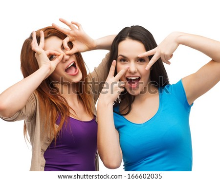 happiness and people concept - two young teenagers making funny faces - stock photo
