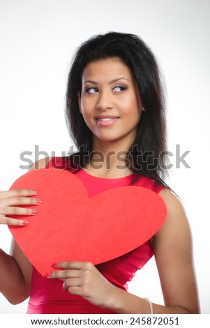 Happiness and valentines day concept. Fashion young woman holding red heart card. Girl mixed race african caucasian in fashionable red dress posing with love symbol on gray - stock photo