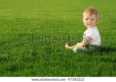 Happiness Baby boy sitting on the grass in field - stock photo