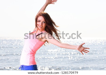 Happiness bliss freedom concept. Woman happy smiling joyful with arms up dancing on beach in summer during holidays travel. Beautiful young cheerful Caucasian female model