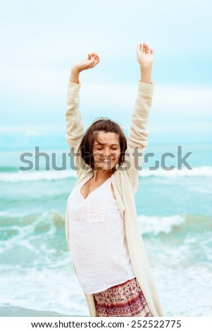 Happiness bliss freedom concept. Woman happy smiling joyful with arms up dancing on beach in summer during holidays travel. - stock photo