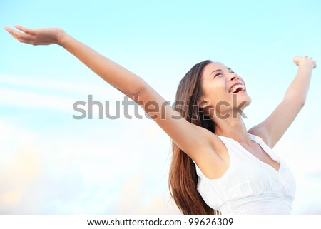 Happiness bliss freedom concept. Woman happy smiling joyful with arms up dancing on beach in summer during holidays travel. Beautiful young cheerful mixed race Asian Chinese / Caucasian female model. - stock photo