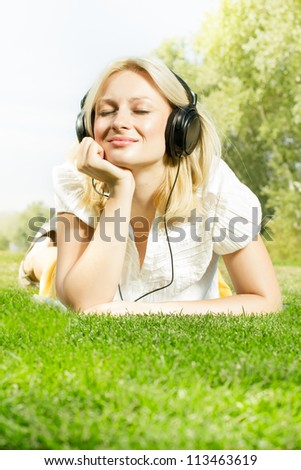 Happiness blonde woman with headphones relaxing on green grass in the park. - stock photo