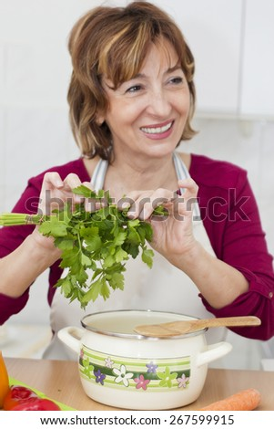 Happiness brown haired mature woman cooking in the kitchen.She  holding a fresh parsley and looking away. Focus on foreground. - stock photo