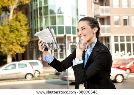 happiness businesswoman, good news in newspaper - stock photo