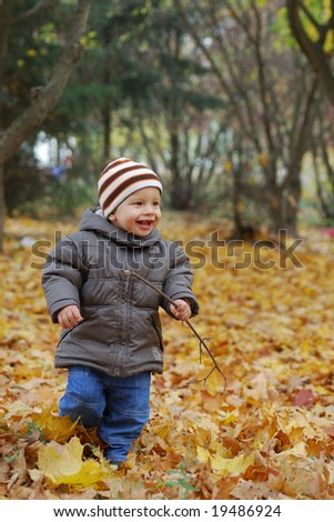 happiness child playing in autumn forest - stock photo
