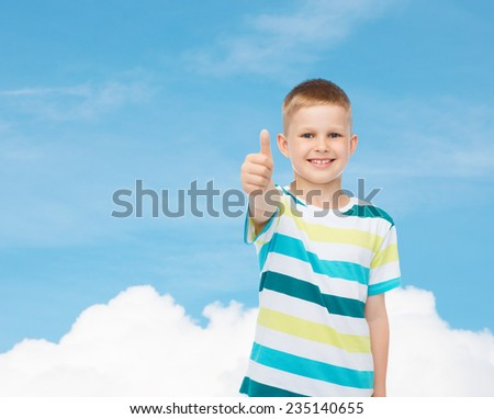 happiness, childhood and people concept - smiling little boy in casual clothes showing thumbs up over blue sky background - stock photo