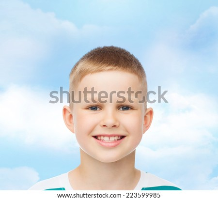 happiness, childhood, dreams and people concept - smiling little boy over blue cloudy sky background